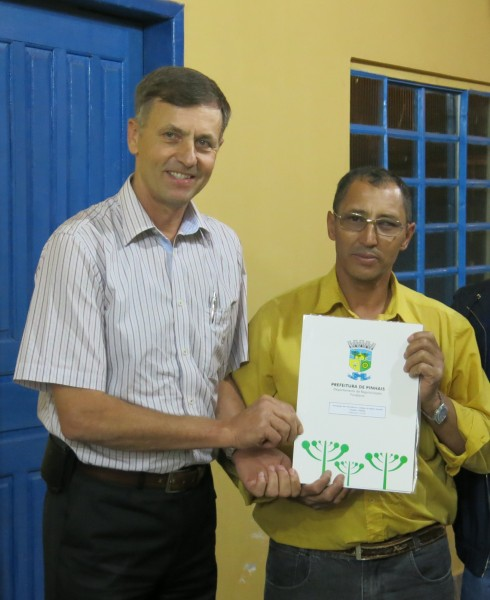 Mr. Antônio Florêncio Brandão gets the title to the association's lot from Mayor Luizão Goularte. The lot was donated to the association by the former owners for the development of community activities.